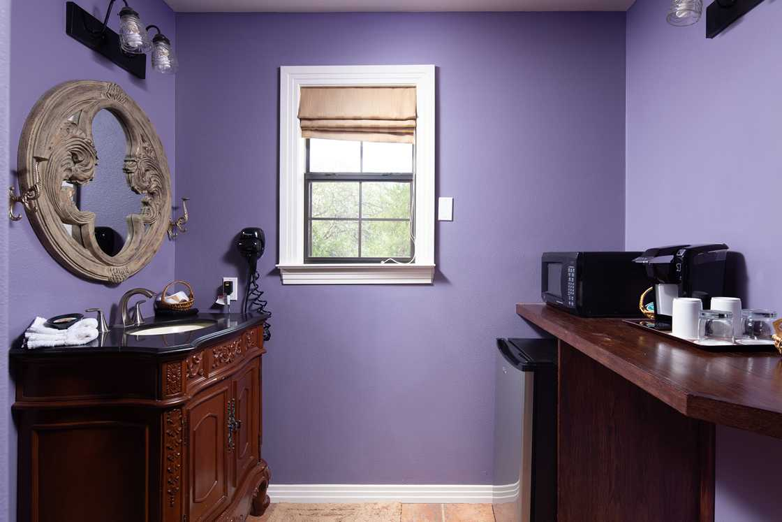 wide shot of purple bathroom vanity area and window