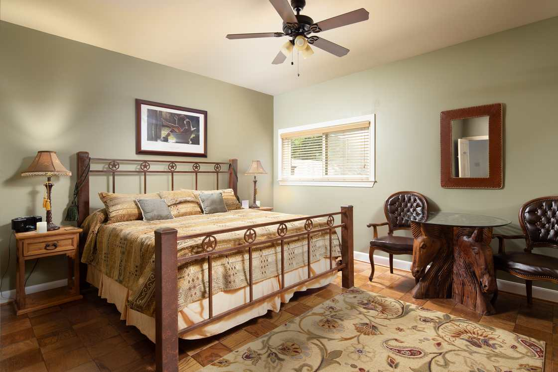 western themed room with green walls and king bed