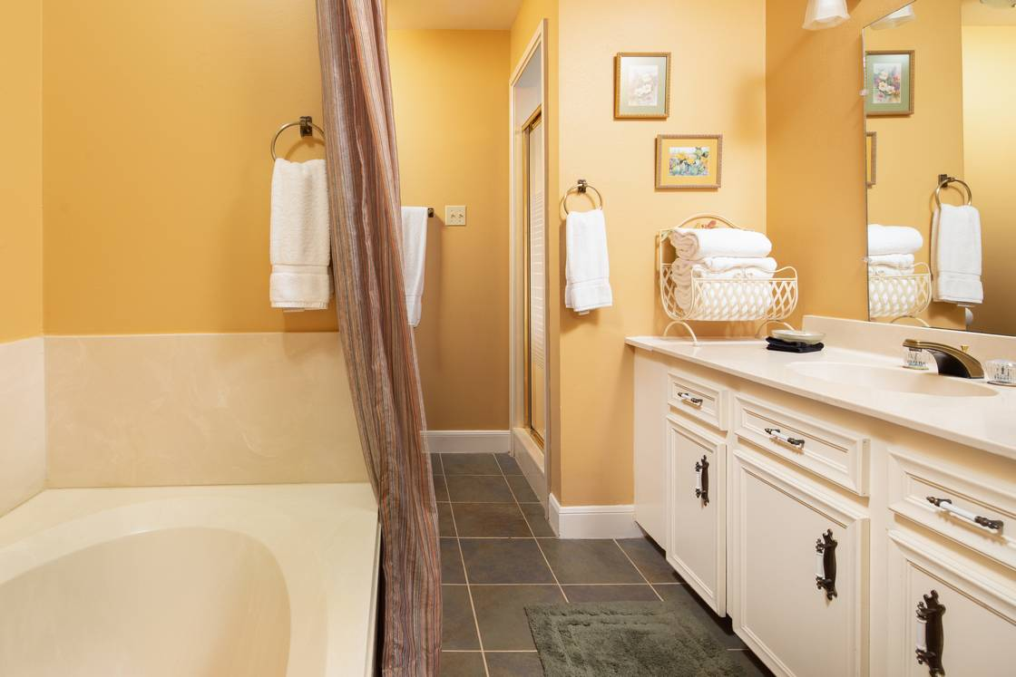 yellow and white bathroom vanity and tub