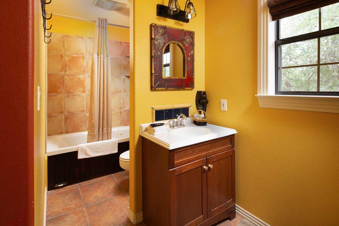 wide shot of yellow bathroom vanity and tiled tub