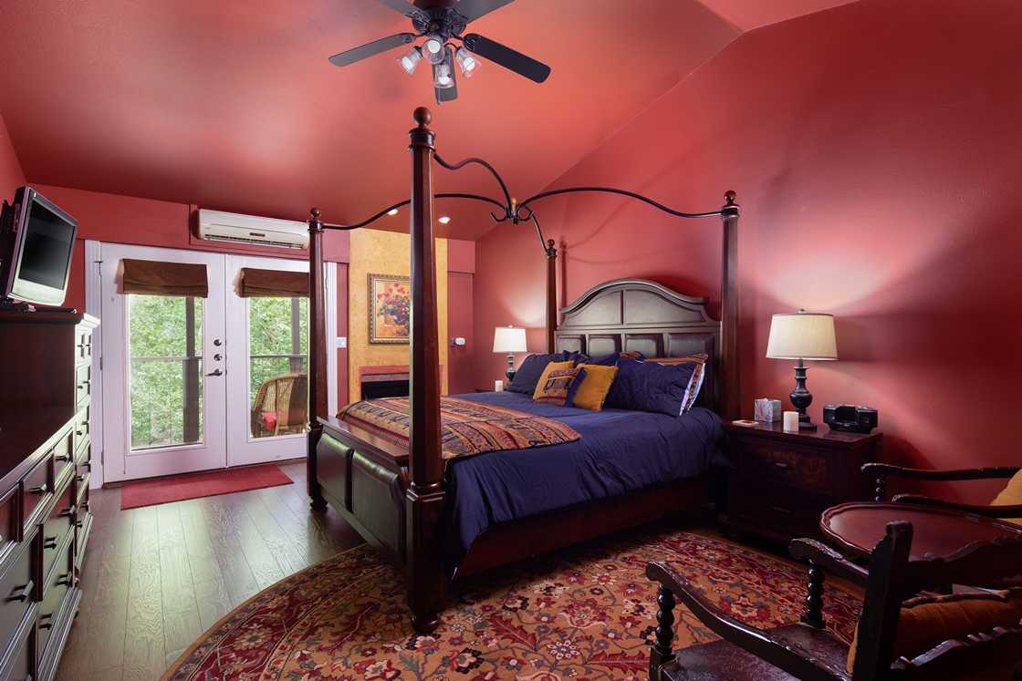 wide shot of red bedroom with purple four poster bed