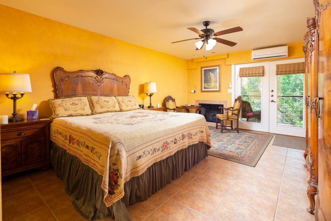 wide shot of yellow walled bedroom, wood headboard, fireplace and sliding patio doors.