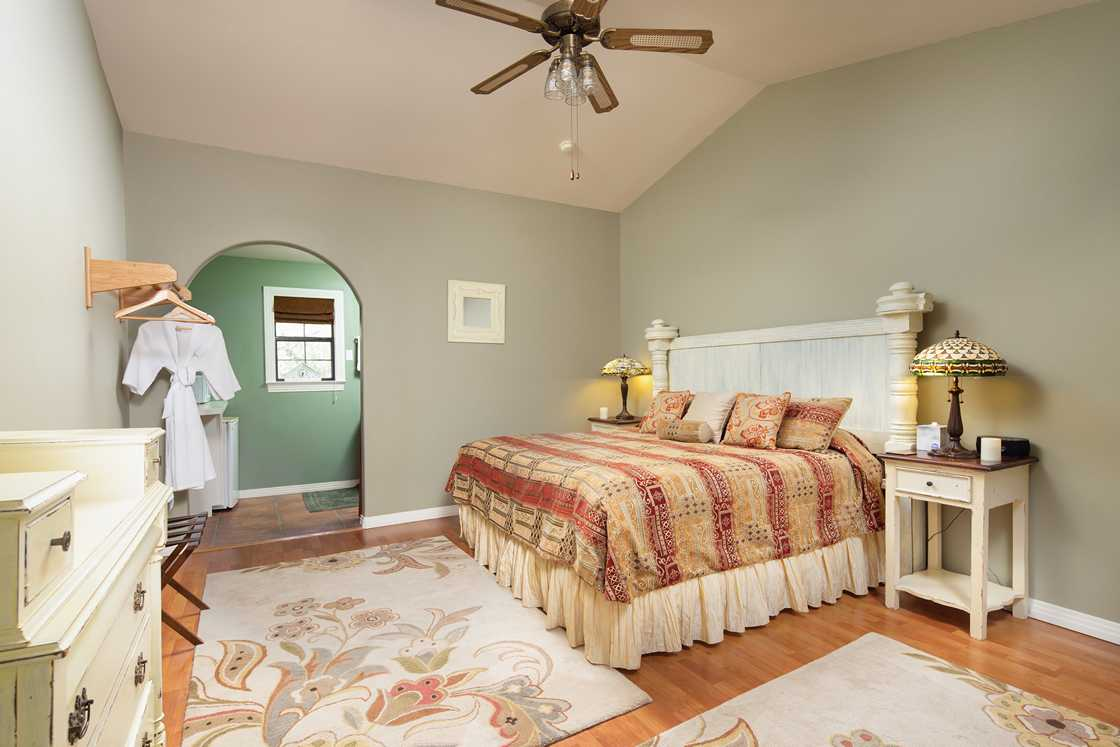 narrow image of sage colored walls, white headboard and red bedspread and colorful rugs