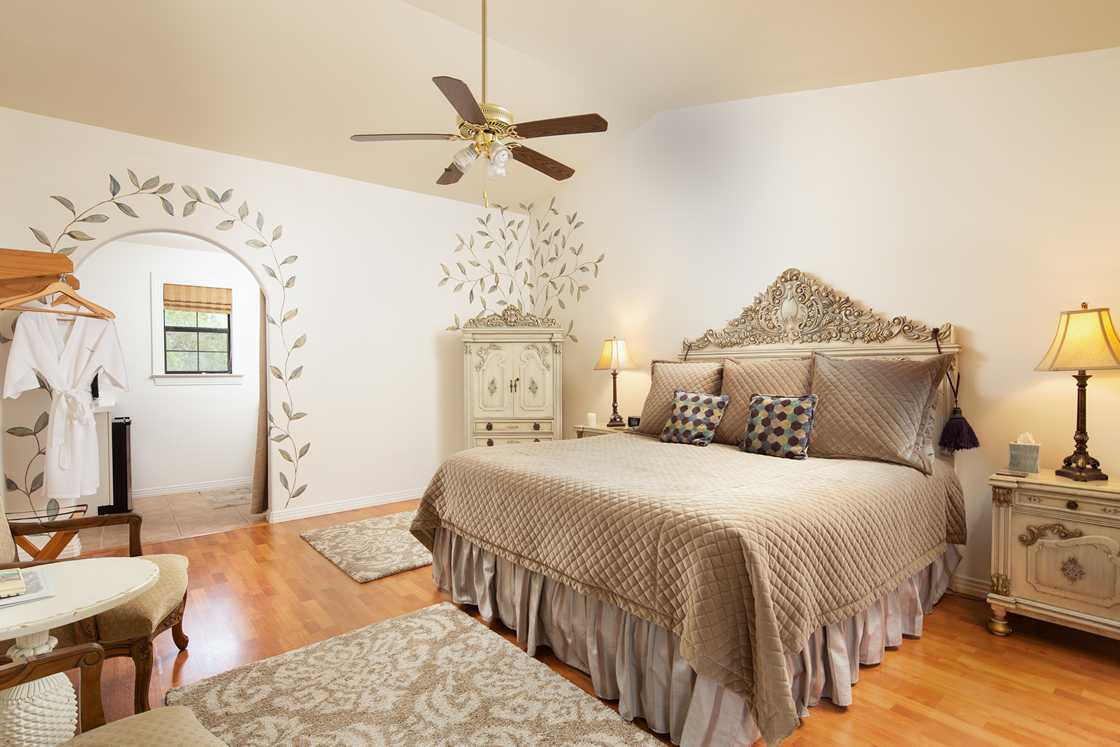 wide shot of white bedroom with olive leaves painted on wall and brown bed