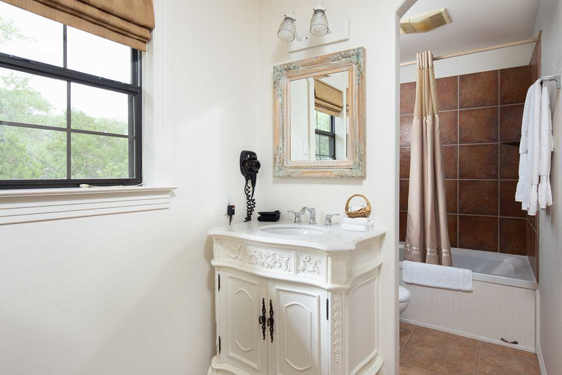 wide shot of a mostly white bathroom, brown tile shower and a window