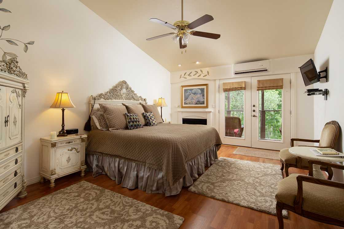 floor to ceiling of a white bedroom with rugs, and a brown bed